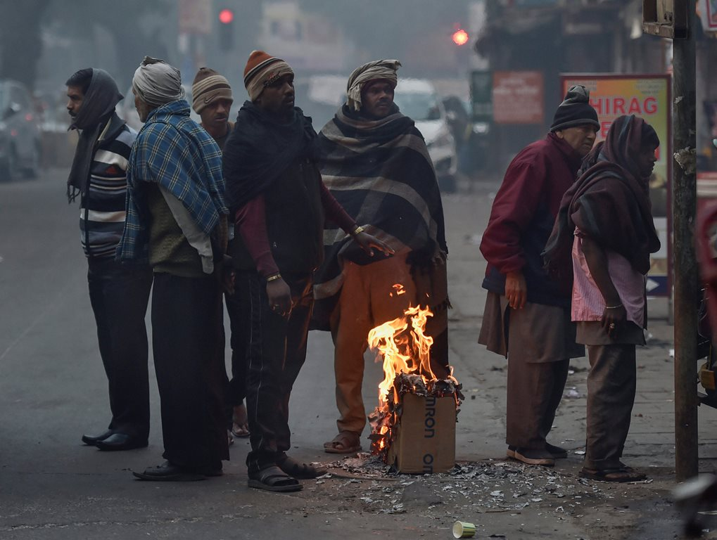 New Delhi: People gather around a makeshift bonfire to warm themselves on a cold, foggy morning, in New Delhi, Sunday, Dec. 23, 2018. (PTI Photo/Ravi Choudhary) (PTI12_23_2018_000065)