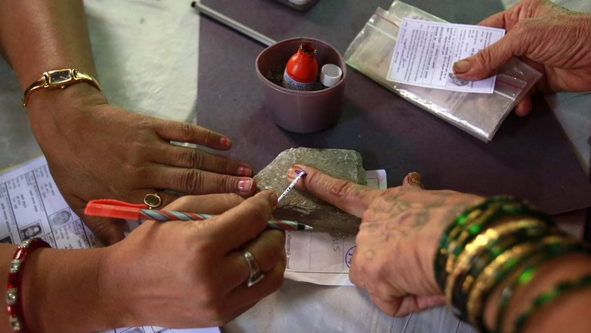 A polling officer applies ink on the finger of a voter at a polling centre during Maharashtra state elections, in Mumbai October 15, 2014. REUTERS/Danish Siddiqui (INDIA - Tags: POLITICS ELECTIONS) - RTR4A8A9