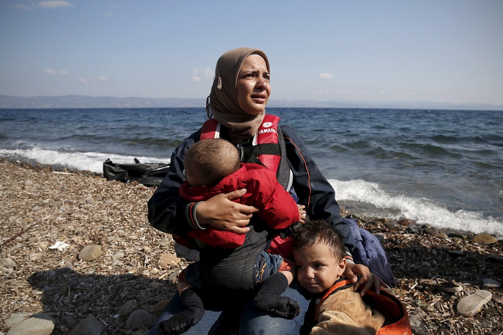 A Syrian woman cries while holding her children moments after arriving on a dinghy on the island of Lesbos, Greece August 23, 2015. Photo by Alkis Konstantinidis/Reuters.