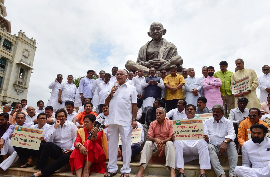 Bengaluru: Karnataka BJP State President B S Yeduyurappa with his party MLAs sits in front Gandhi statue for a protest to demand the resignation of Karnataka Chief Minister H D Kumaraswamy at Vidhana Soudha, in Bengaluru, Wednesday, July 10, 2019. (PTI Photo/Shailendra Bhojak)(PTI7_10_2019_000057B)
