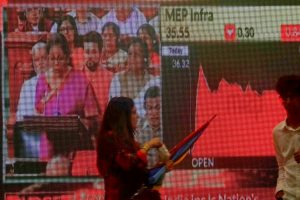 People walk as a telecast of India's Finance Minister Nirmala Sitharaman presenting the budget is displayed inside the Bombay Stock Exchange (BSE) building in Mumbai, July 5, 2019. Image: Reuters/Francis Mascarenhas