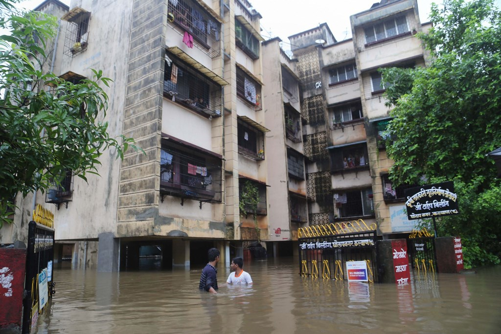 Thane: People wade across a waterlogged street after incessant monsoon rainfall, in Thane, July 27, 2019. (PTI Photo) (PTI7_27_2019_000119B)