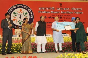 The Prime Minister, Shri Narendra Modi presenting the award to Ms. Sonia Chauhan for suggesting the name 'Pradhan Mantri Jan Dhan Yojana (PMJDY)', in New Delhi on August 28, 2014.  The Union Minister for Finance, Corporate Affairs and Defence, Shri Arun Jaitley, the Minister of State for Commerce & Industry (Independent Charge), Finance and Corporate Affairs, Smt. Nirmala Sitharaman, the Principal Secretary to Prime Minister, Shri Nripendra Misra, the Governor of Reserve Bank of India, Shri Raghuram Rajan and other dignitaries are also seen.