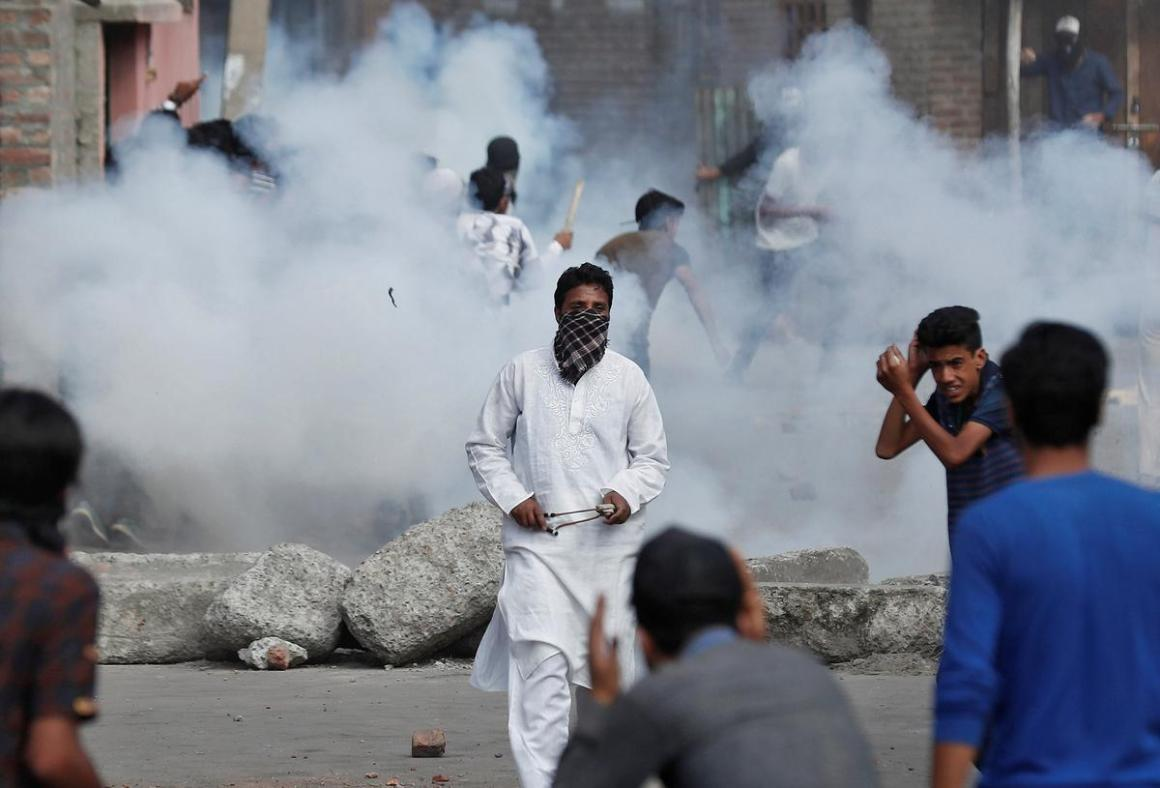 Kashmiris run for cover as smoke rises from teargas shells fired by Indian security forces during clashes, after scrapping of the special constitutional status for Kashmir by the Indian government, in Srinagar, August 23, 2019. REUTERS/Adnan Abidi