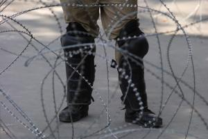 FILE PHOTO: An Indian police officer stands behind the concertina wire during restrictions on Eid-al-Adha after the scrapping of the special constitutional status for Kashmir by the Indian government, in Srinagar, August 12, 2019. REUTERS/Danish Ismail