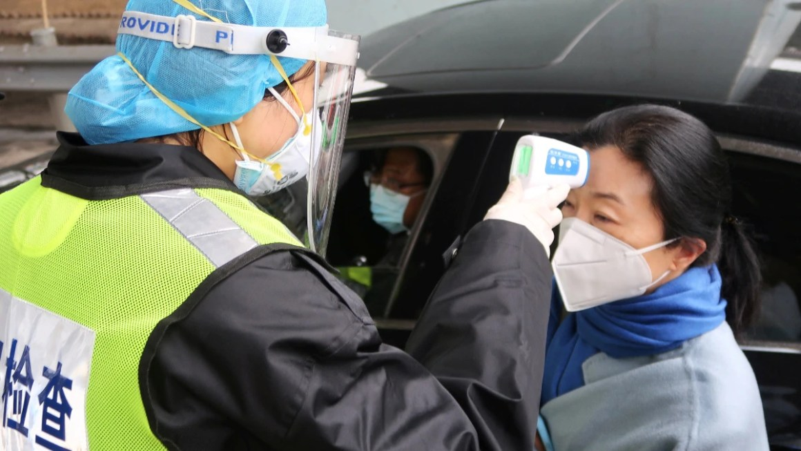 A security officer in a protective mask checks the temperature of a passenger at an expressway toll station in Xianning, Hubei province, China, January 24, 2020. (Photo: Reuters)