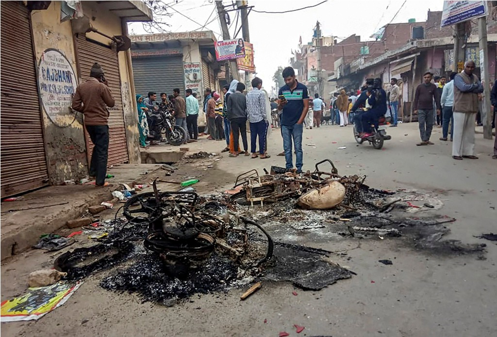 **EDS: BEST QUALITY AVAILABLE**New Delhi: Passersby look at the charred remains of vehicles which were set ablaze by rioters during clashes over the new citizenship law, at Mustafabad area of East Delhi, Tuesday, Feb. 25, 2020. (PTI Photo/ Sachin Saini)(PTI2_25_2020_000093B)