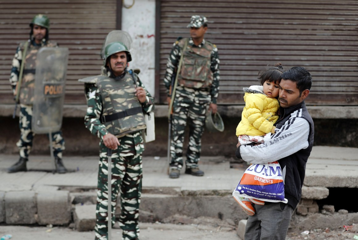 A man carrying a child walks past security forces in a riot affected area following clashes between people demonstrating for and against a new citizenship law in New Delhi, February 27, 2020. REUTERS/Adnan Abidi