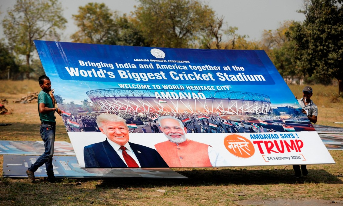 Ahmedabad: Workers carry a hoarding with pictures of the U.S. President Donald Trump and India's Prime Minister Narendra Modi as preparations are underway for Trump's forthcoming 'Namaste Trump' event, in Ahmedabad, Wednesday, Feb. 19, 2020. (PTI Photo)  (PTI2_19_2020_000126B)