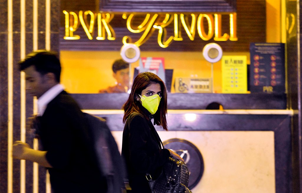 New Delhi: People wearing mask to mitigate the spread of coronavirus, walk past a cinema hall, in New Delhi, Thursday, March 12, 2020. Cinema halls in Delhi will be shut till March 31 as a preventive measure following Coronavirus outbreak. (PTI Photo/Vijay Verma) (PTI12-03-2020_000215B)