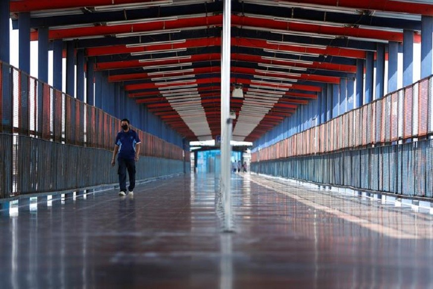 A man wearing a protective mask walks on a bridge at a railway station during lockdown by the authorities to limit the spreading of coronavirus disease (COVID-19), in New Delhi. (Reuters)