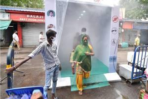Kolkata: People pass through a sanitisation tunnel installed at the entrance of Bhawanipore market, during ongoing COVID-19 lockdown in Kolkata, Friday, April 24, 2020. (PTI Photo/Swapan Mahapatra) (PTI24-04-2020 000067B)