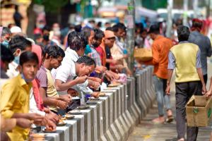 New Delhi: People consume meals distributed by volunteers during a nationwide lockdown in the wake of coronavirus outbreak, at Shakur Basti in North West Delhi, Friday, April 3, 2020. (PTI Photo/Vijay Verma)(PTI03-04-2020_000166B)