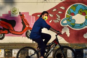 New Delhi: A woman cycles past a wall graffiti during the COVID-19 lockdown in New Delhi, Sunday, April 26, 2020. (PTI Photo/Manvender Vashist) (PTI26-04-2020_000177B)