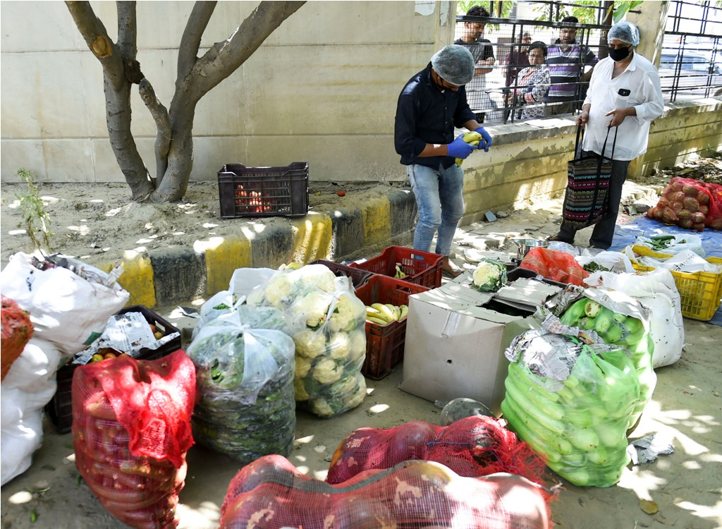 Ghaziabad: A vendor sells vegetables at the sealed KDP society, identified as a COVID-19 hotspot, during the nationwide lockdown to curb the spread of coronavirus, in Ghaziabad, Friday, April 10, 2020. (PTI Photo/Arun Sharma)(PTI10-04-2020_000158B)