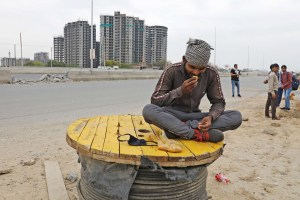 A migrant worker eats food offered by the local residents on a highway as he and others are returning to their villages, after India ordered a 21-day nationwide lockdown to limit the spreading of coronavirus disease in Ghaziabad March 2020. (Photo: Reuters)