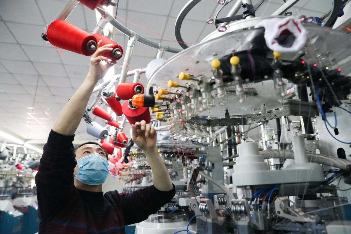 An employee wearing a face mask works on a production line manufacturing socks for export at a factory in Huzhou's Deqing county, Zhejiang province, China February 19, 2020. China Daily via REUTERS