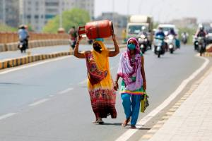 Ahmedabad: A woman carries a cooking gas cylinder on her head as she walks on a bridge during the ongoing nationwide COVID-19 lockdown, in Ahmedabad, Saturday, May 9, 2020. (PTI Photo)(PTI09-05-2020 000089B)