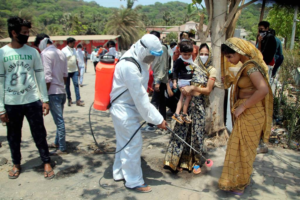Mumbai: A worker wearing a protective suit sprays disinfectant on the feet of a migrant leaving for Rajasthan from Vasai Creek, off the national highway in Mumbai, Thursday, May 14, 2020. (PTI Photo)(PTI14-05-2020 000180B)