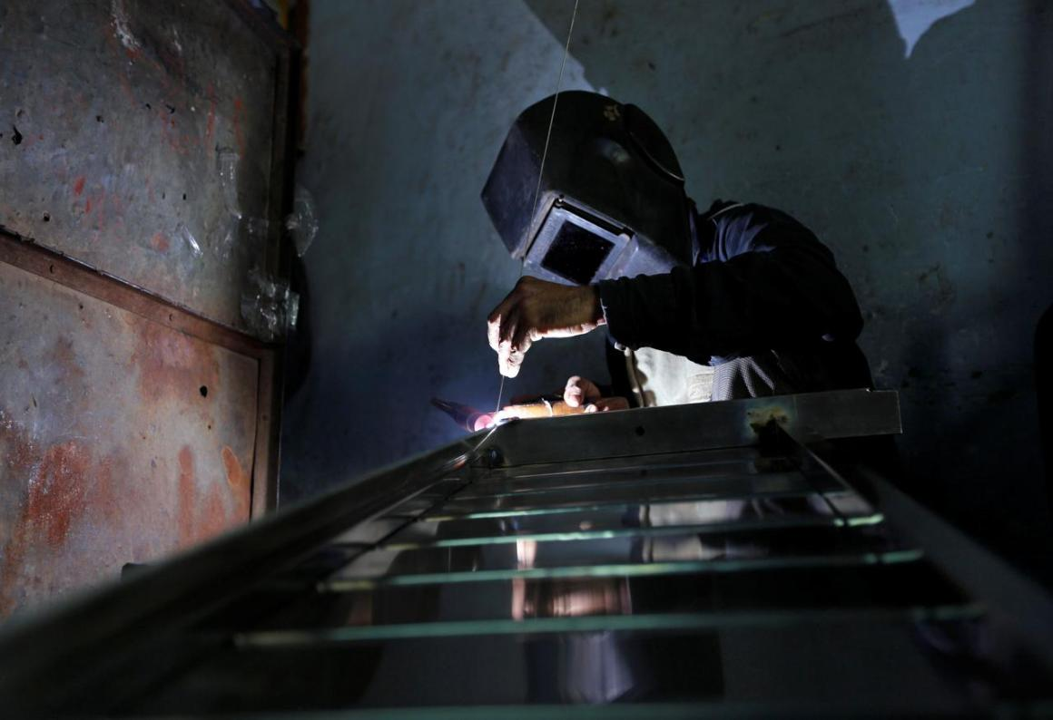 A worker welds steel pipes to make a counter at a steel furniture manufacturing unit in Ahmedabad, India September 1, 2016. REUTERS/Amit Dave/File Photo