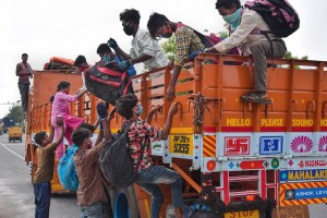 Vijayawada: Migrants climb onto a truck to reach to their native place in Bihar, during the ongoing COVID-19 nationwide lockdown, in Vijayawada, Tuesday, May 19, 2020. (PTI Photo)(PTI19-05-2020 000074B)