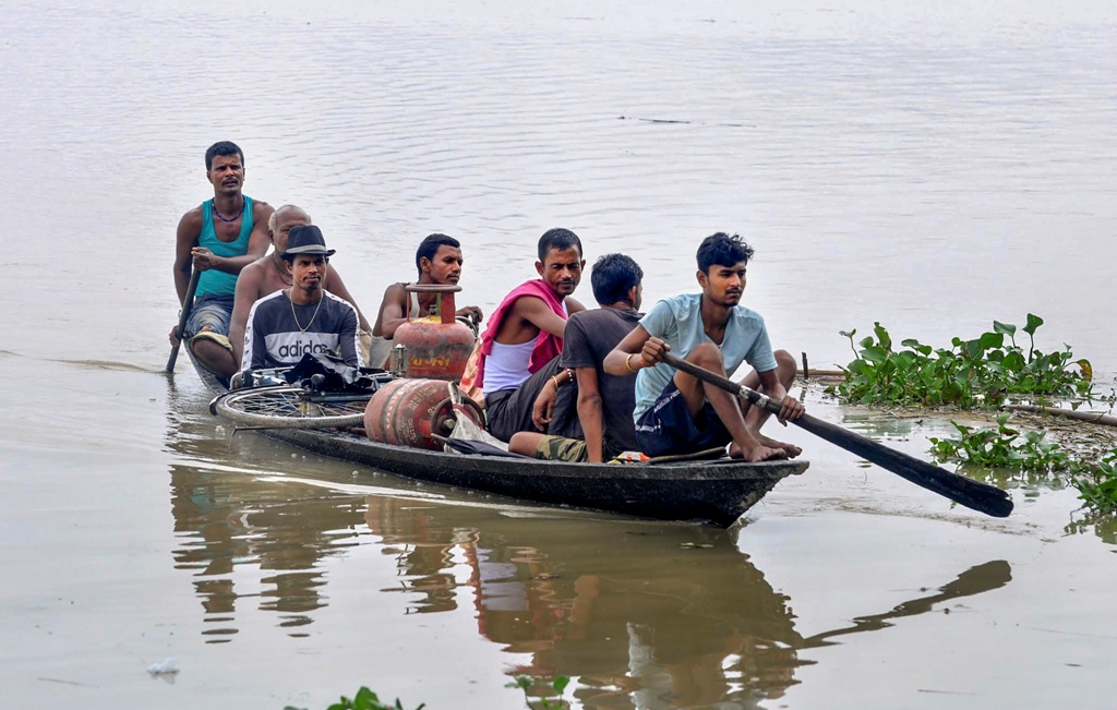 Morigaon: Villagers cross a flooded area by a boat, at Sildubi village in Morigaon district of Assam, Sunday, July, 2020. (PTI Photo) (PTI12-07-2020 000060B)