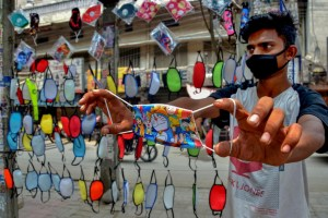 Amritsar: A salesman shows a designer face mask at his roadside stall, during Unlcok 2.0, in Amritsar, Saturday, July 18, 2020. (PTI Photo)(PTI18-07-2020 000066B)