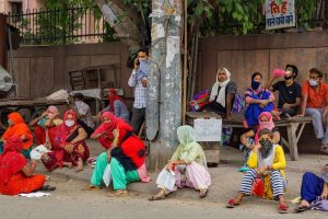 Women wait outside a fair price shop to collect free ration in East Delhi. Photo: PTI/Kamal Kishore