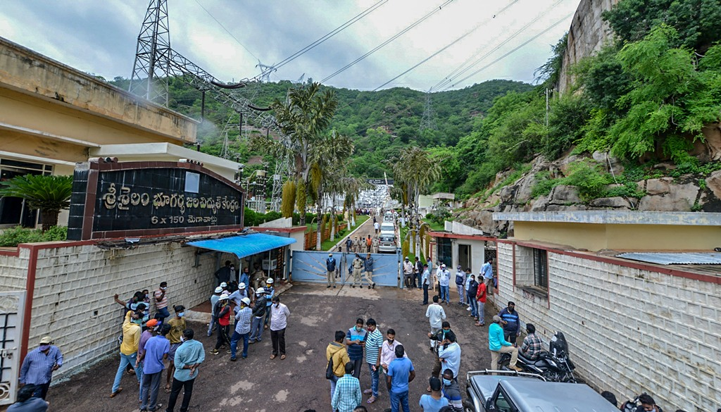 Kurnool: Police and locals gather outside Srisailam Left Bank Power Station (SLBP) after a fire broke out on Thursday night, at Srisailam in Kurnool district, Friday, Aug. 21, 2020. (PTI Photo)(PTI21-08-2020 000104B)