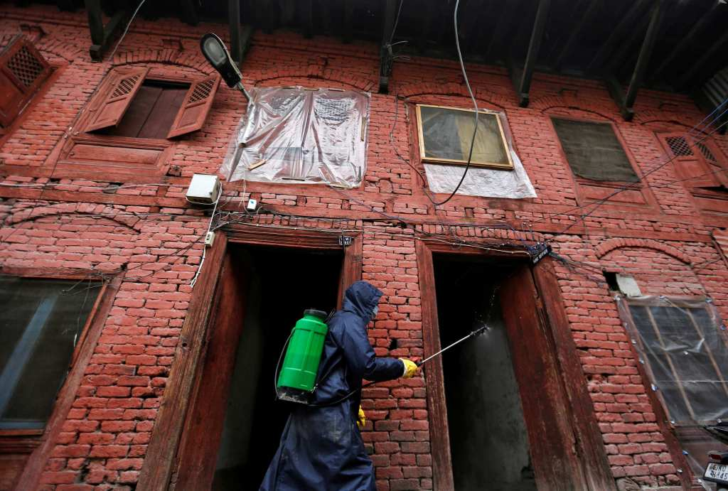 A municipal worker wearing a protective suit disinfects the premises of a police station in Srinagar. (Credit: Reuters)