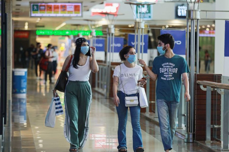 People wearing masks walk with shopping bags inside a mall as India eases lockdown restrictions that were imposed to slow the spread of the coronavirus disease (COVID-19), in New Delhi, India, June 8, 2020. REUTERS/Anushree FadnavisREUTERS