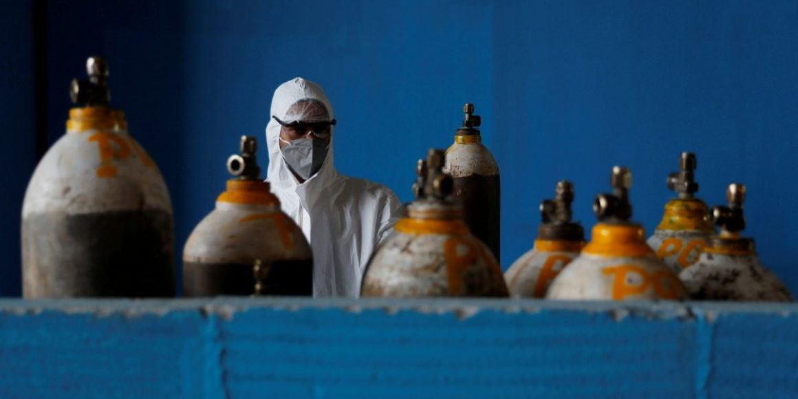 A medical worker stands next to an oxygen cylinder at the Yatharth Hospital in Noida, on the outskirts of New Delhi, India, September 15, 2020. Photo: Reuters/Adnan Abidi