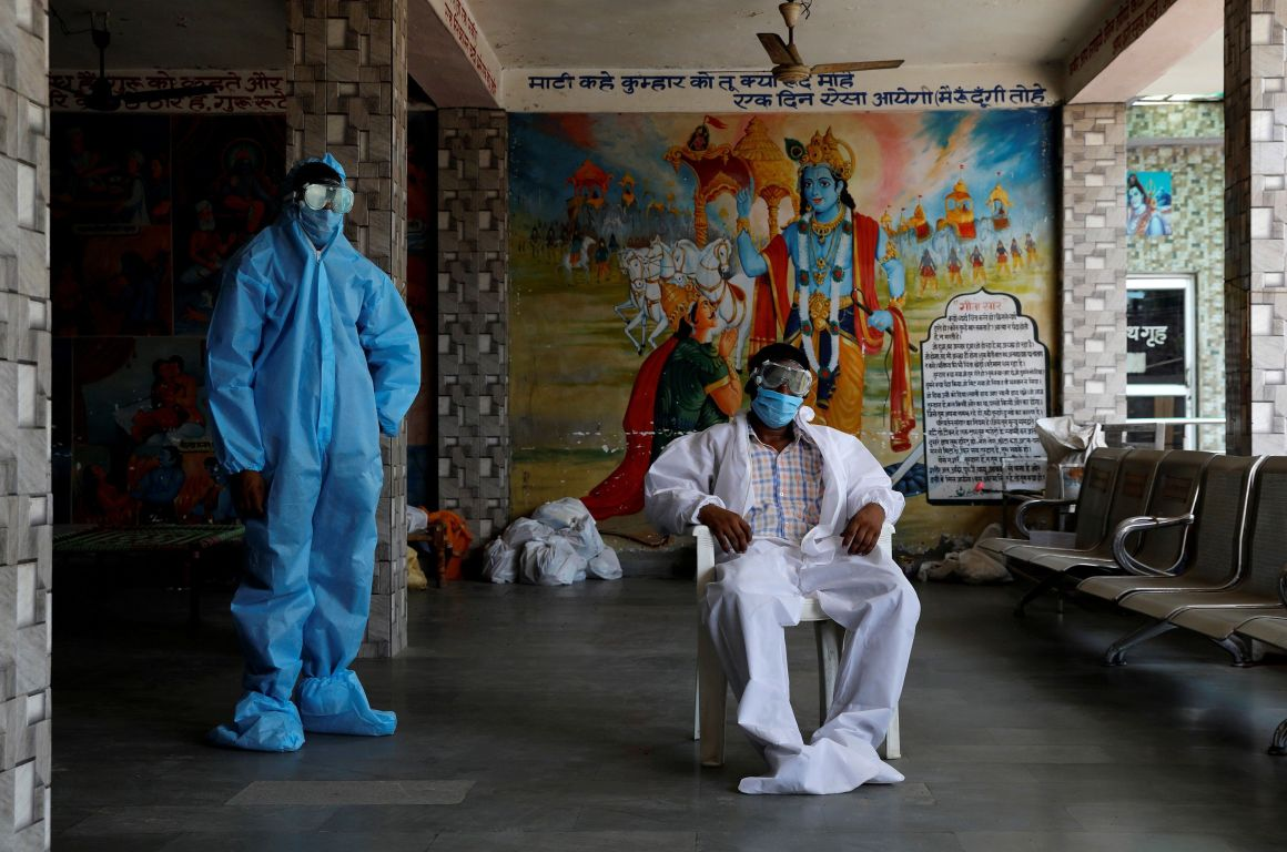 A priest and a labourer wear PPE at a crematorium in New Delhi, India, July 3, 2020. Photo: REUTERS/Anushree Fadnavis