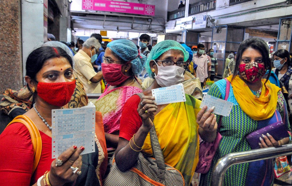 Kolkata: Passengers show their tickets before boarding a local train after the authorities resumed its services from today onwards with certain restrictions, amid the coronavirus pandemic, at Sealdah station in Kolkata, Wednesday, Nov. 11, 2020. (PTI Photo)(PTI11-11-2020 000059B)