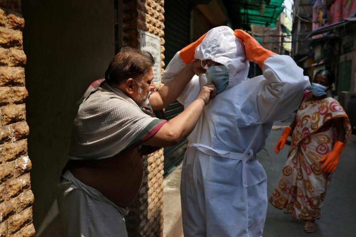 A resident adjusts the face mask of a health worker during a sanitization drive to control the spreading of coronavirus disease (COVID-19), in a neighbourhood in Kolkata, April 16, 2020. REUTERS/Rupak De Chowdhuri