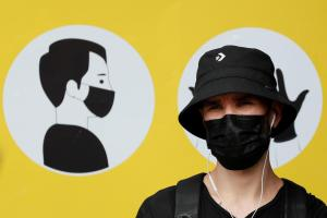 A man wearing a protective face mask amid the outbreak of the coronavirus disease (COVID-19) stands in front of a social poster in central Kyiv, Ukraine July 30, 2020. REUTERS/Gleb Garanich/File Photo