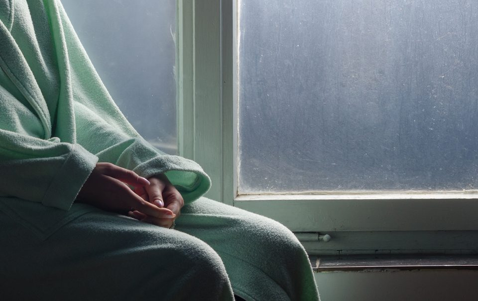 Young cancer patient sitting in front of hospital window.