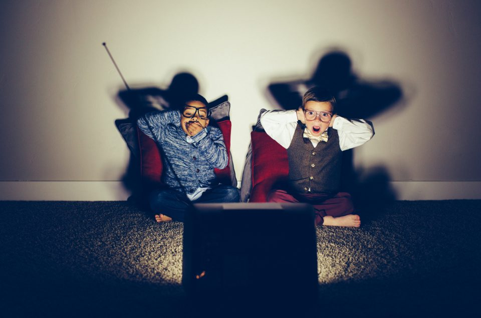 Two young boy nerds dressed in bow ties sit in a basement late at night on a weekend watching a television show that is using vulgarity. They are both surprised and covering mouths and ears to keep from seeing and hearing the changing standards of television.