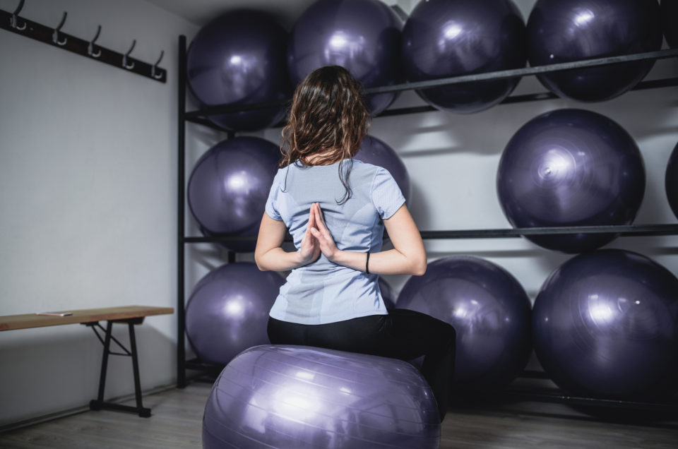 Athlete Female Take Meditation Position on Exercise Ball at the Gym