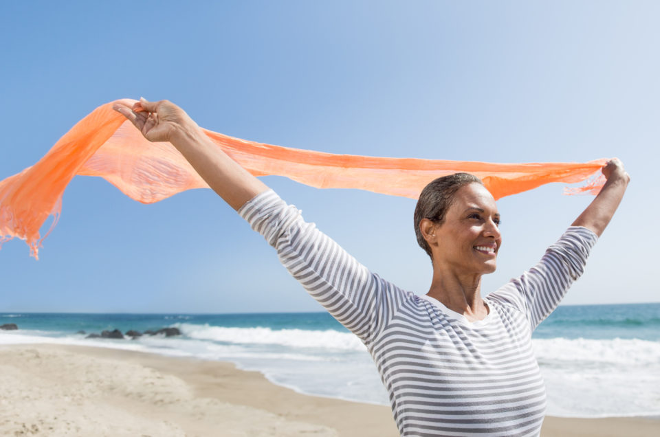 Happy senior woman enjoying the wind on the beach. iStockalypse LA California
