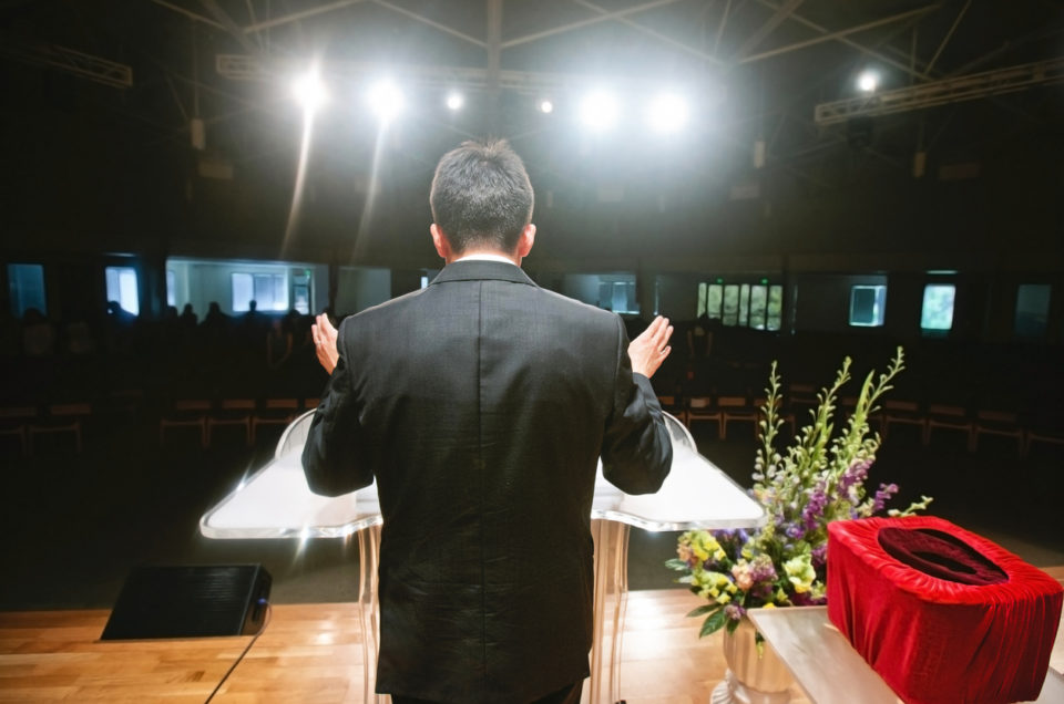 A pastor stands behind the pulpit in front of a congregation