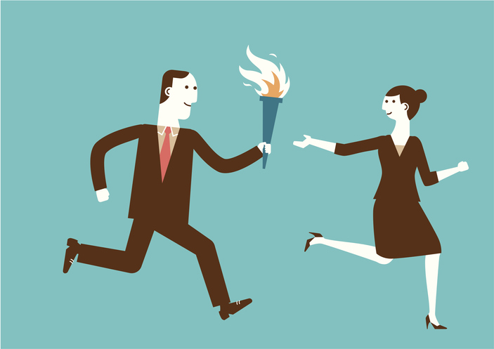 A businessman passing a torch to a businesswoman.