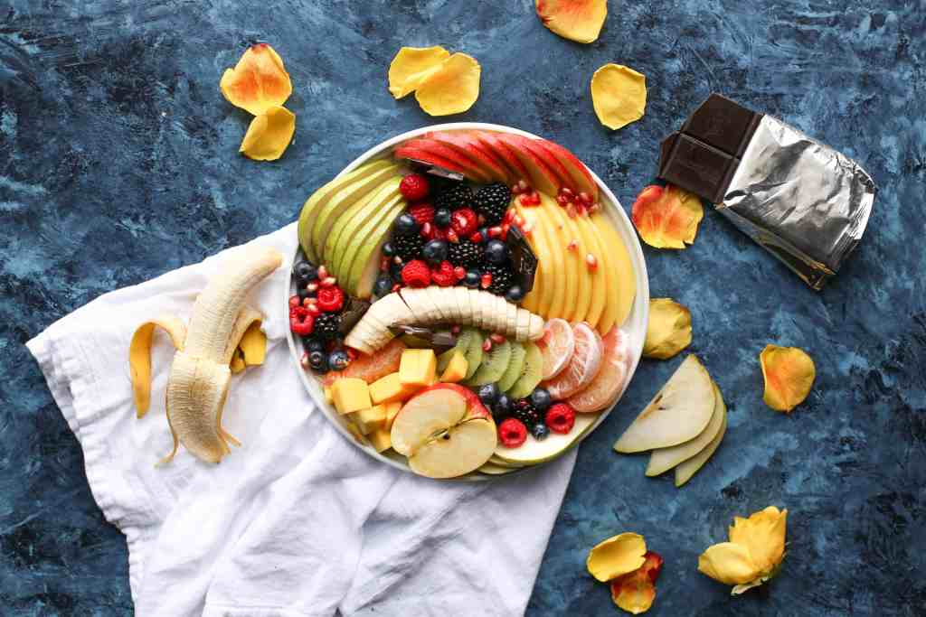 Picture of fresh fruit arranged on a plate surrounded by chocolate bar and more fruit