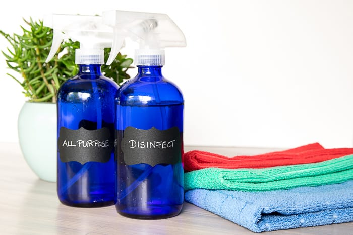 picture of two blue glass spray bottles labeled all purpose and disinfect, bathroom cleaning system