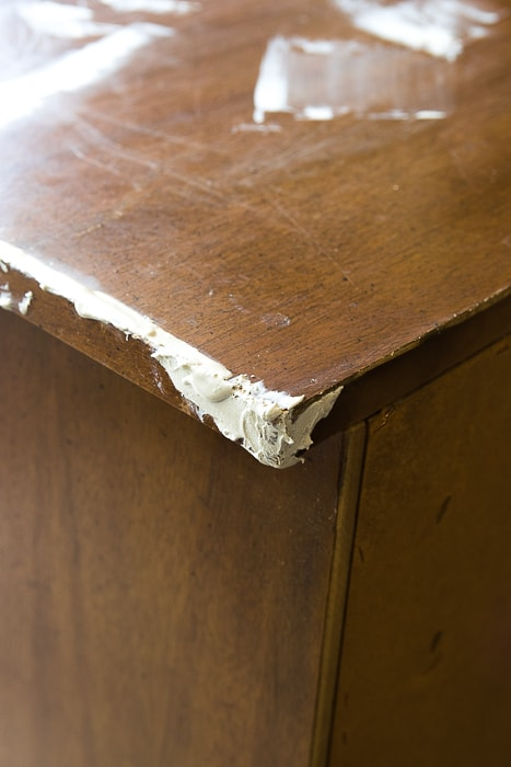 Picture of damaged corner of wood dresser with wood filler