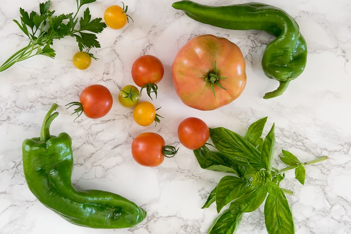 Picture of various size tomatoes, peppers, herbs