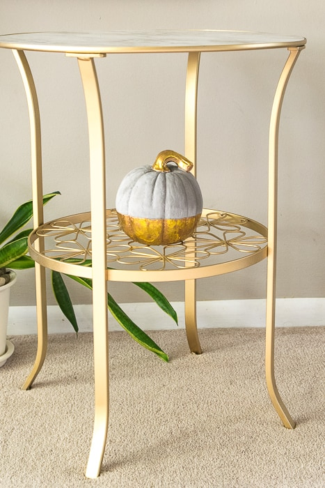 picture of finished gold painted table from side with small concrete and gold pumpkin