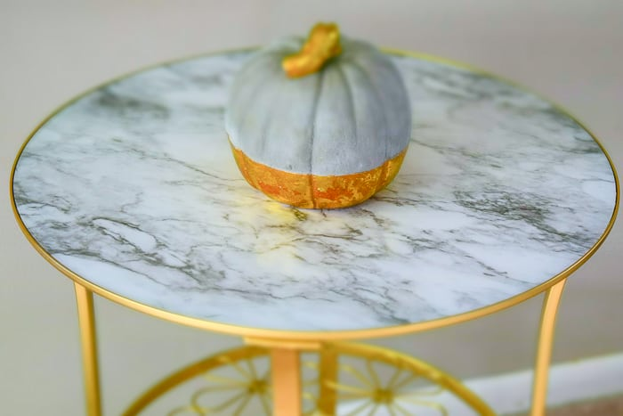 picture showing gold and gray pumpkin on gold table with marble top