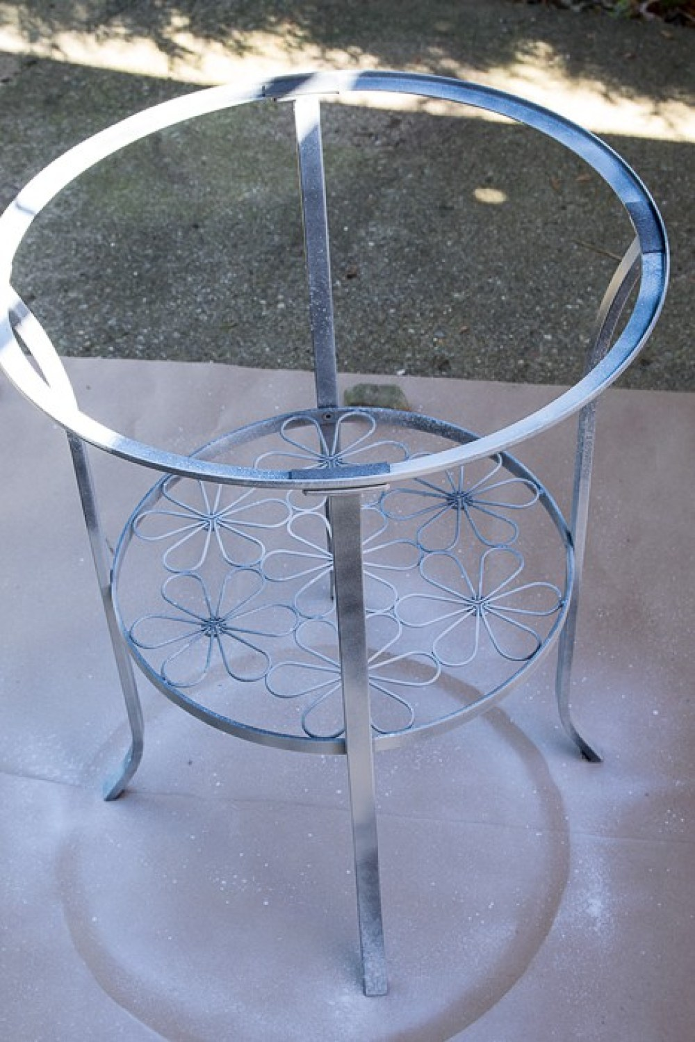 Picture of upright round metal table with primer coat sprayed on