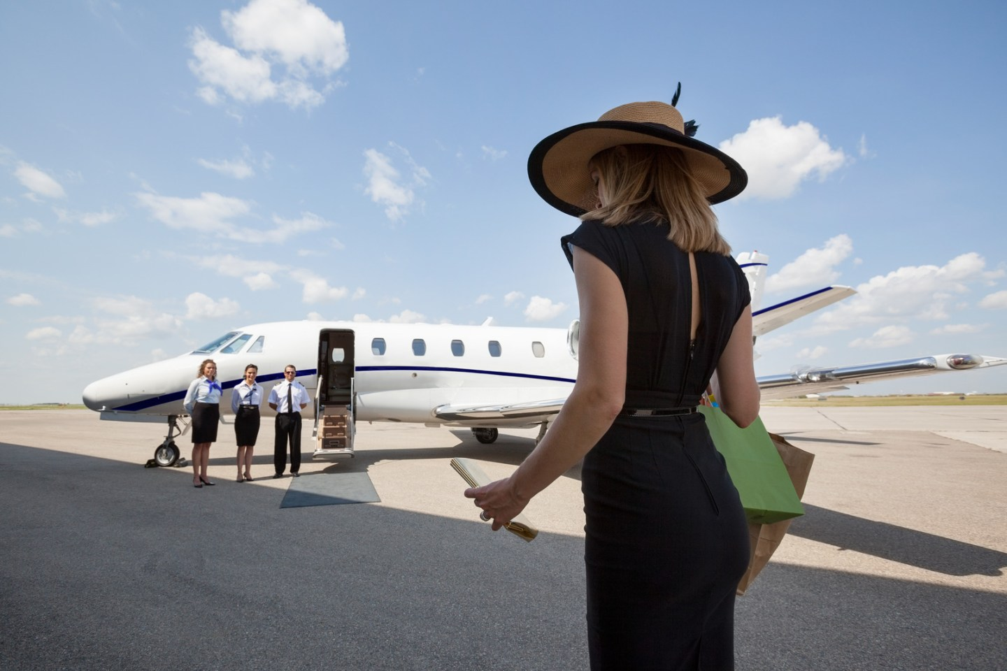 Rear view of woman walking towards pilot and stewardesses against private jet at airport terminal